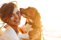 Image of happy woman 20s hugging her dog while sitting on sand by seaside
