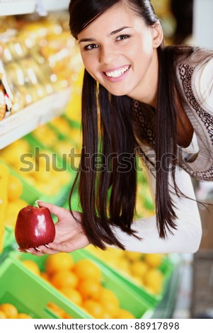 Image of happy woman with fresh apple in hand looking at camera in supermarket - stock photo