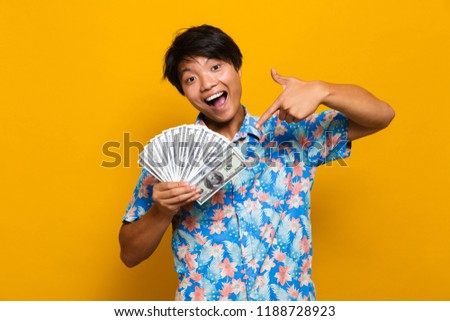 Image of happy young asian man standing isolated over yellow background holding money showing thumbs up.