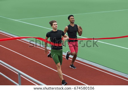 Image of happy young athlete man run on running track outdoors crossing finish line. Looking aside.