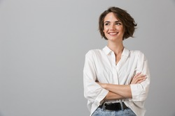 Image of happy young business woman posing isolated over grey wall background.