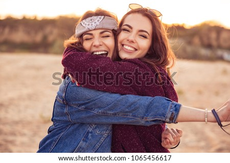 Image of happy young caucasian friends ladies walking outdoors on the beach hugging.