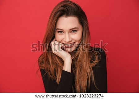 Image of happy young cute woman standing isolated over red background. Looking camera. #1028223274