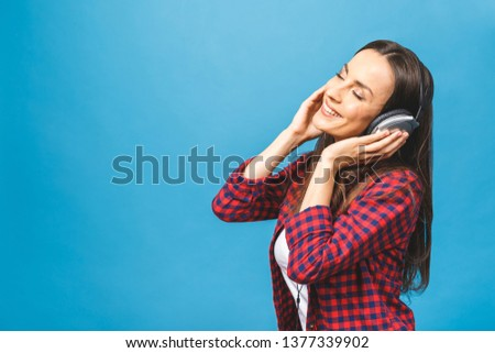 Image of happy young lady standing isolated over blue background. Using phone, listening music in headphones. #1377339902
