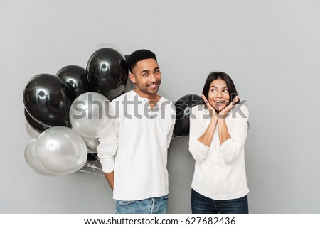 Image of happy young loving couple standing over grey wall and looking at camera. Man holding a lot of balloons.