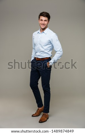 Image of happy young man wearing formal clothes smiling at camera with hands in pockets isolated over gray background