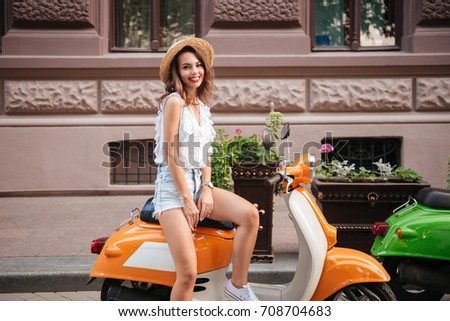 Image of happy young woman outdoors standing near scooter. Looking camera.