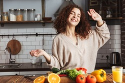 Image of happy young woman smiling while cooking salad with fresh vegetables in kitchen interior at home