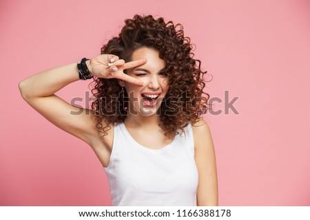 Image of happy young woman standing isolated over pink background showing peace gesture. Looking camera. #1166388178