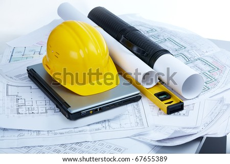 Image of helmet, blueprints, laptop and mechanical tools at workplace