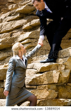Image of helpful man holding businesswoman by hand while standing on the mountain
