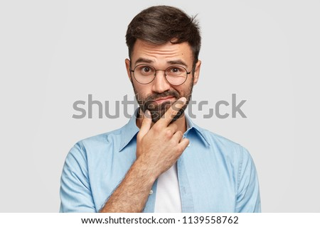 Image of hesitant unshaven European male with thick beard, holds chin, purses lips with clueless expressions, doubts what to eat delicious for supper, isolated over white background. What to choose?