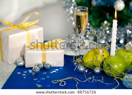 Image of holiday table with flute of champagne, fruits, gifts, burning candle and decorations on it