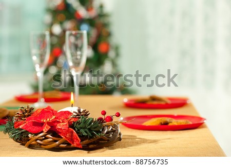 Image of holiday wreath with flutes and plates at background on Christmas table