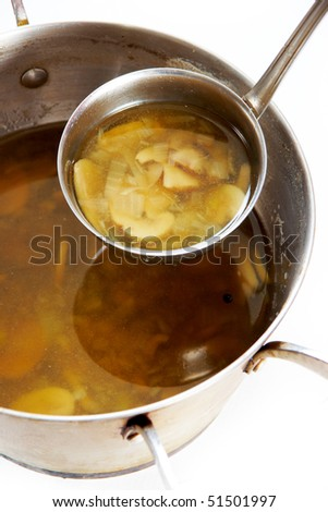 Image of hot soup in pan and ladle