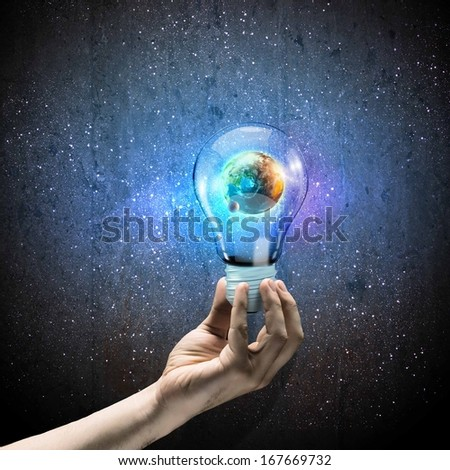 Image of human hand holding bulb with earth planet inside Elements of this image are furnished by NASA