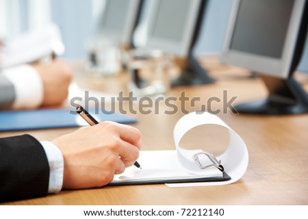 Image of human hand holding pen and making notes with monitors near by