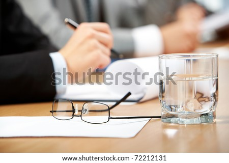 Image of human hand holding pen with glass of water, eyeglasses and paper near by