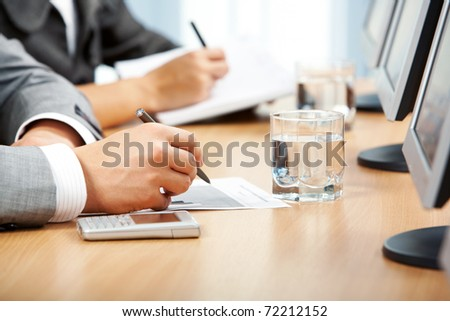 Image of human hand making notes with glass of water, cellphone and monitors near by