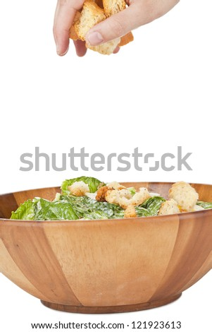 Image of human hand putting croutons on a bowl of Caesar salad over the white surface