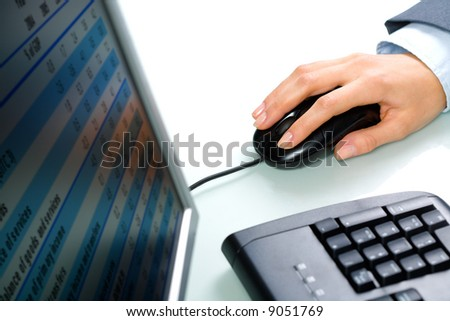 Image of human hand touching a computer mouse with keyboard and monitor near by