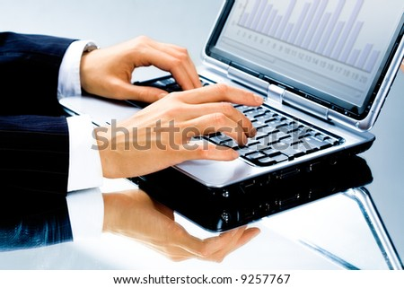 Image of human hand typing a business document on the laptop