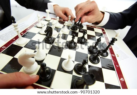 Image of human hand with chess figure making move