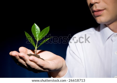 Image of human hand with green sprout at background of man