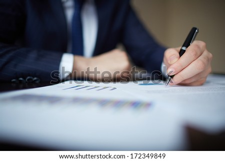 Image of human hand with pen over documents at workplace