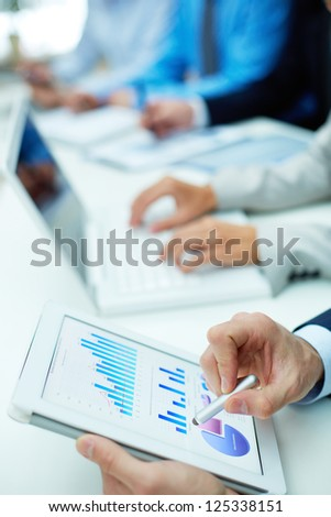 Image of human hand with pointer over business document in touchscreen at meeting