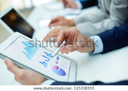 Image of human hand with pointer over business document in touchscreen at meeting - stock photo