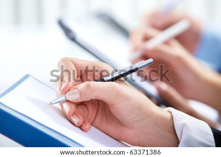 Image of human hand writing on paper at seminar or conference