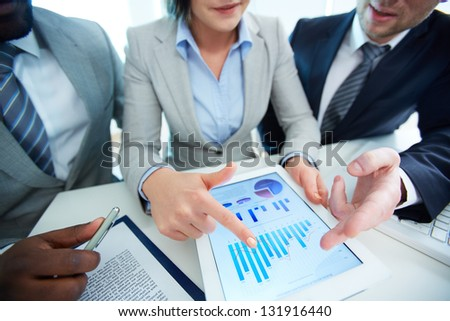 Image of human hands during discussion of business document in touchscreen at meeting