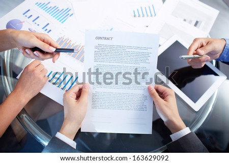 Image of human hands during discussion of contract at meeting