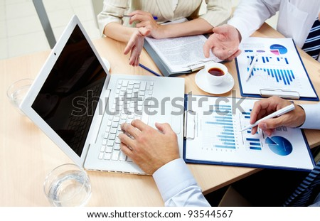 Image of human hands during work with laptop and business documents at meeting