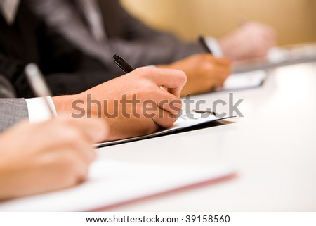 Image of human hands making notes or writing business plan