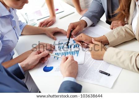 Image of human hands over business documents at meeting