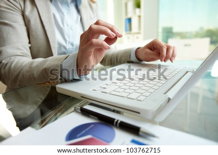 Image of human hands over laptop keyboard