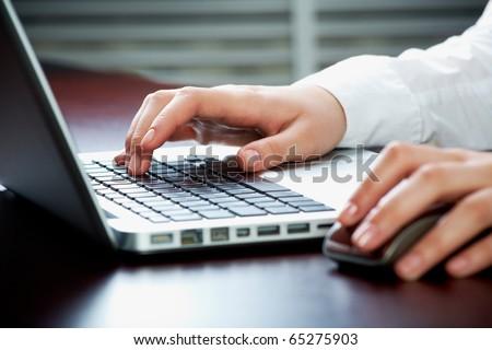 Image of human hands pressing keys of laptop