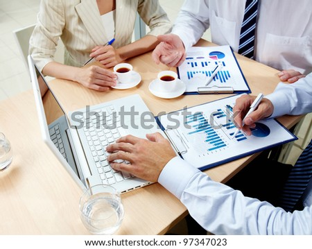 Image of human hands with business documents and laptop at meeting
