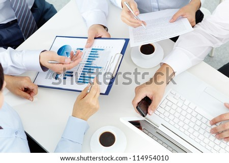 Image of human hands with pens over business documents at meeting - stock photo
