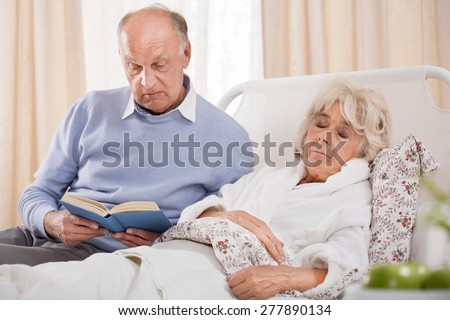 Image of husband reading ill wife book
