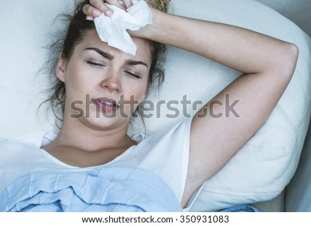 Image of ill woman with headache resting in bed