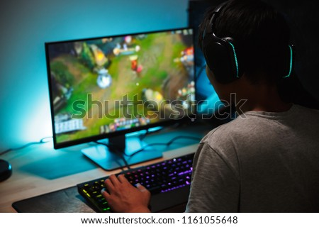 Image of immersed teenage gamer boy playing video games on computer in dark room wearing headphones and using backlit colorful keyboard