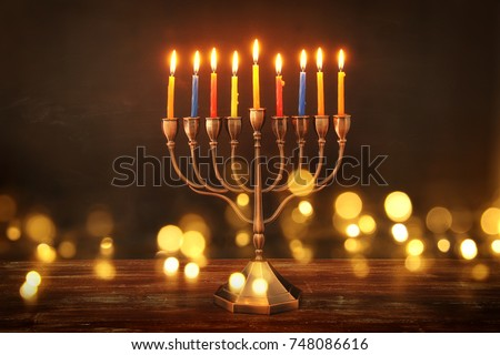 image of jewish holiday Hanukkah background with menorah (traditional candelabra) and burning candles. glitter overlay