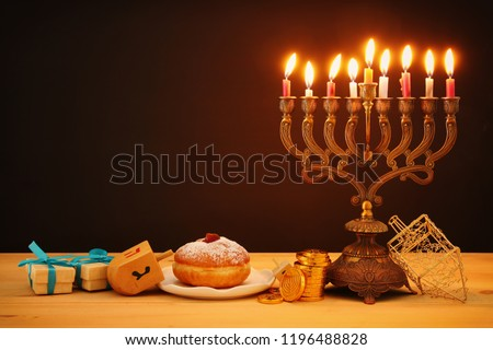image of jewish holiday Hanukkah background with traditional spinnig top, menorah (traditional candelabra) and burning candles