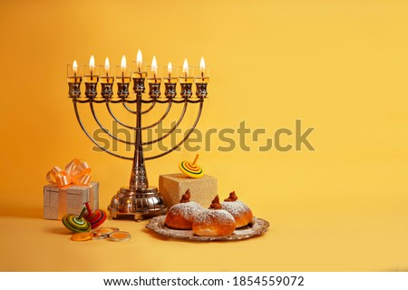 Image of Jewish holiday Hanukkah with menorah (traditional Candelabra), donuts and wooden dreidels (spinning top), doughnut, chocolate coins on a yellow background. Сток-фото ©