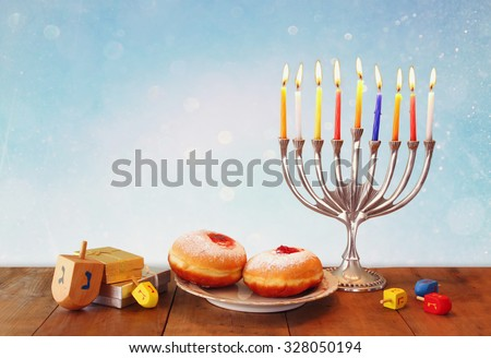 image of jewish holiday Hanukkah with menorah (traditional Candelabra), donuts and wooden dreidels (spinning top). glitter overlay