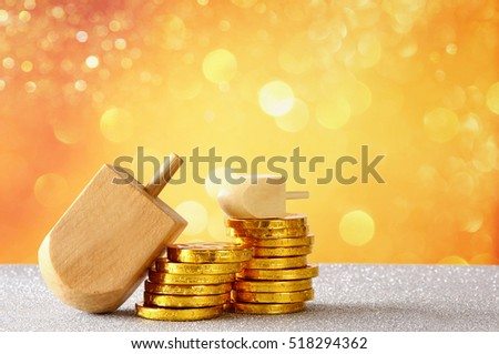 Image of jewish holiday Hanukkah with wooden dreidel (spinning top) and chocolate coins on the glitter background