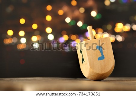Image of jewish holiday Hanukkah with wooden dreidel (spinning top) and gold lights on the table - Shutterstock ID 734170651